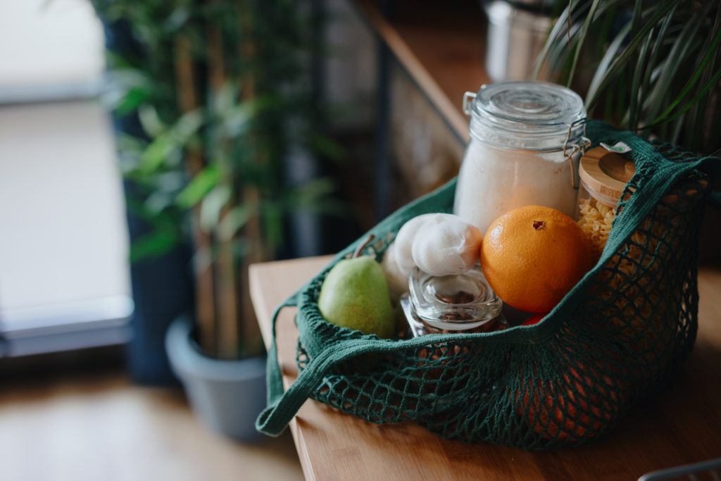 Eco bag on kitchen counter with food in jars and fresh fruits